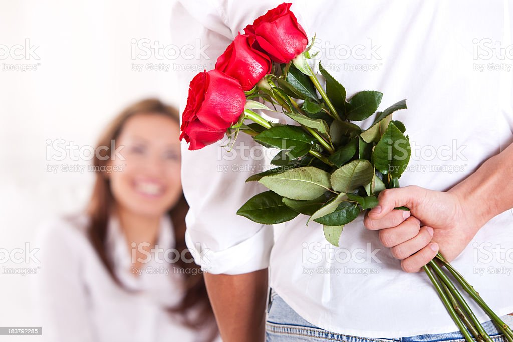 Young man holding bouquet of red roses behind back stock photo