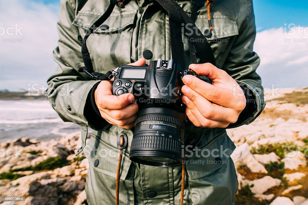 Young man holding camera stock photo