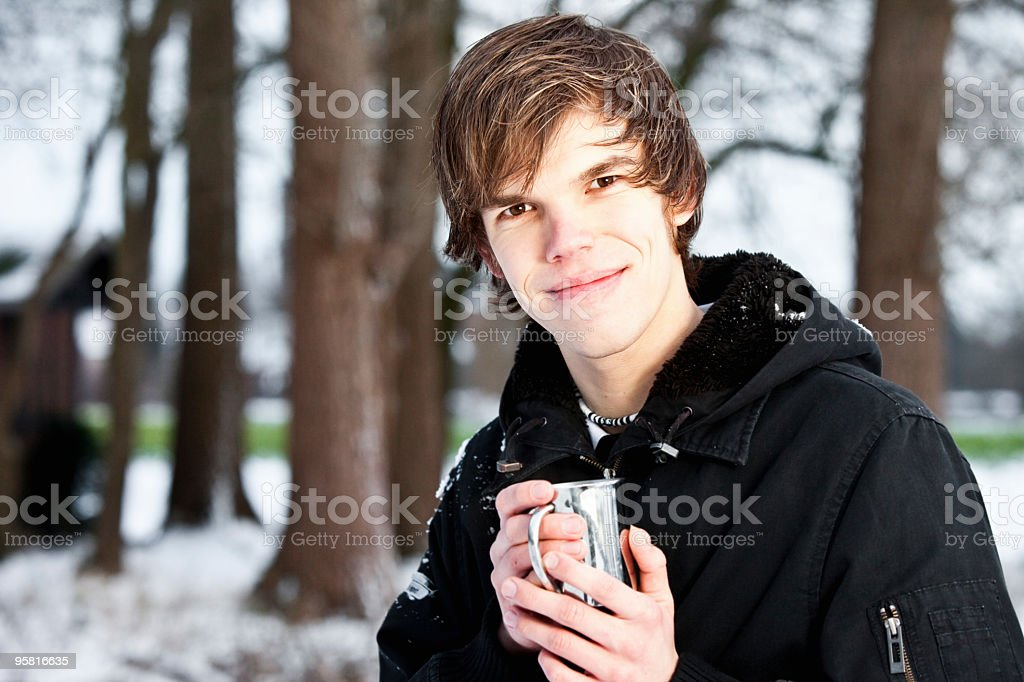 Young man holding cup with a hot drink stock photo