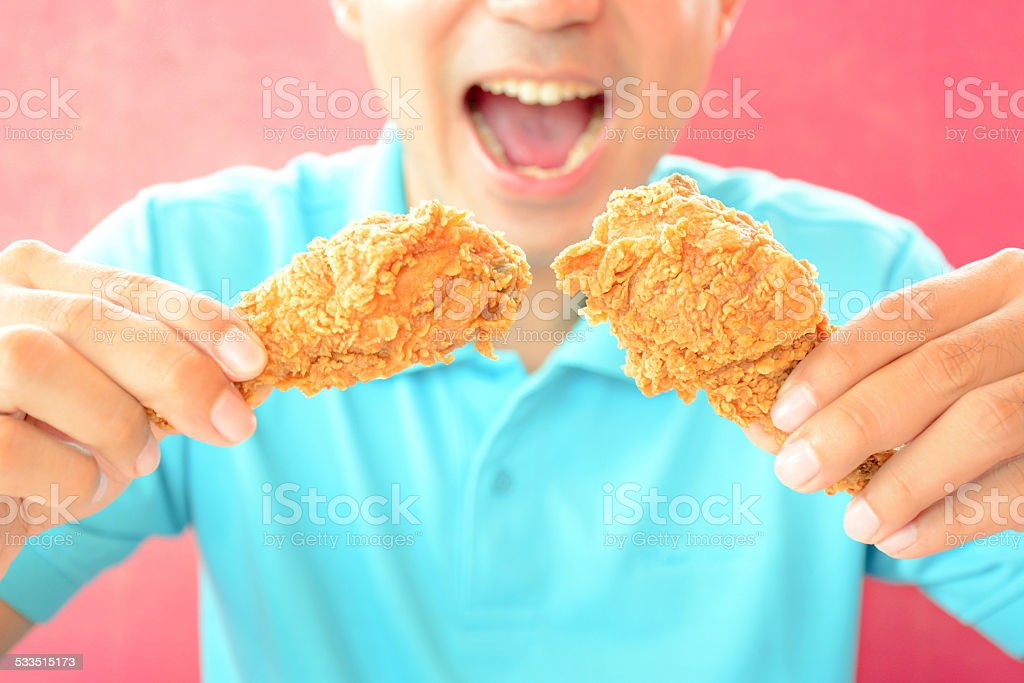 Young man holding  fried chicken legs, about to eat stock photo