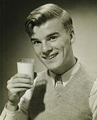 Young man holding glass of milk, smiling, (B&W), portrait