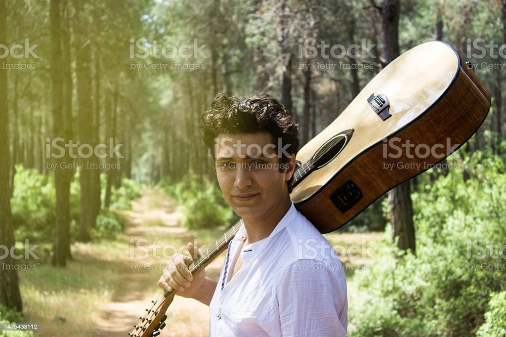 Young man holding guitar on shoulders posing on woodland stock photo