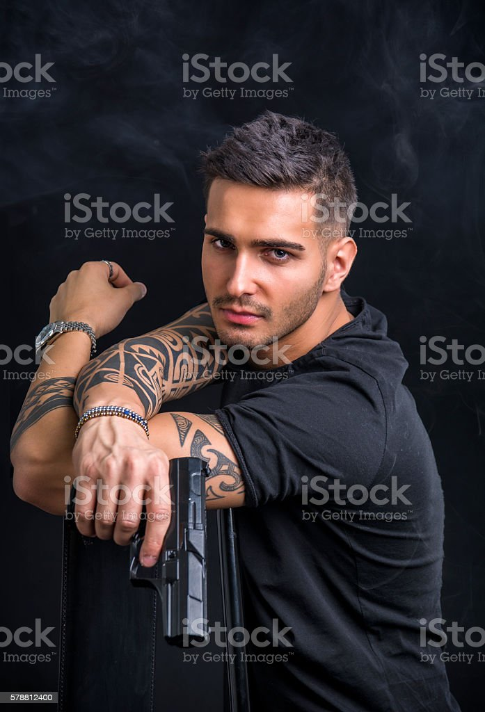 Young man holding hand gun stock photo