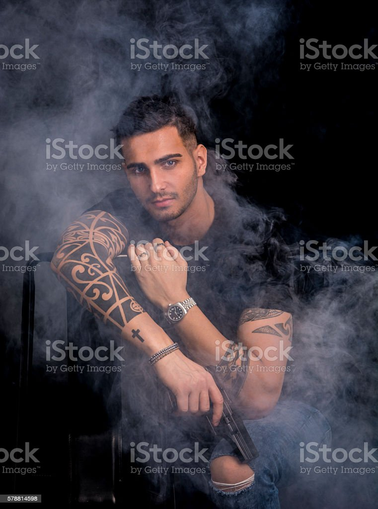 Young man holding hand gun stock photo