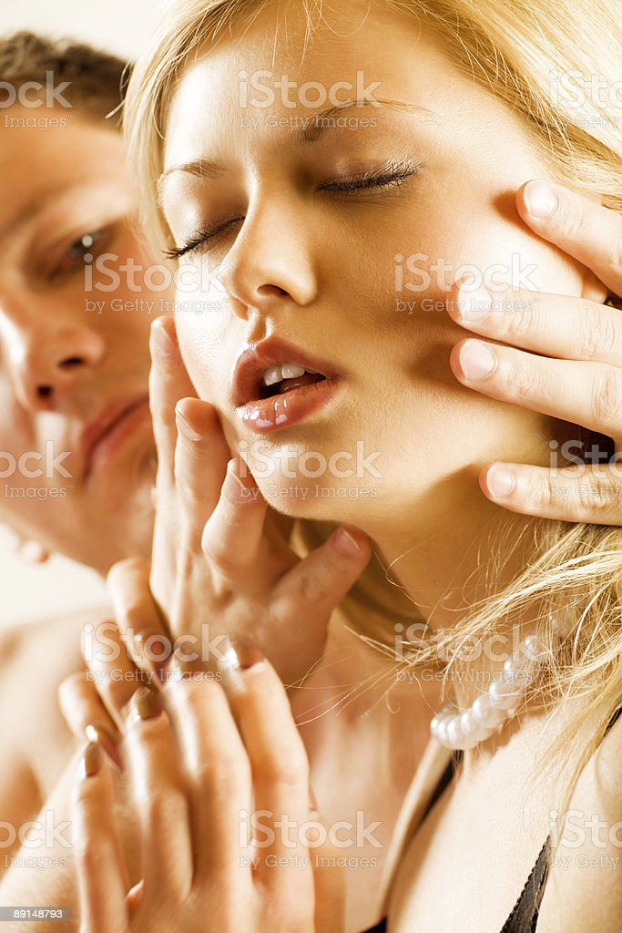 Young man holding head of blond woman, erotic royalty-free stock photo