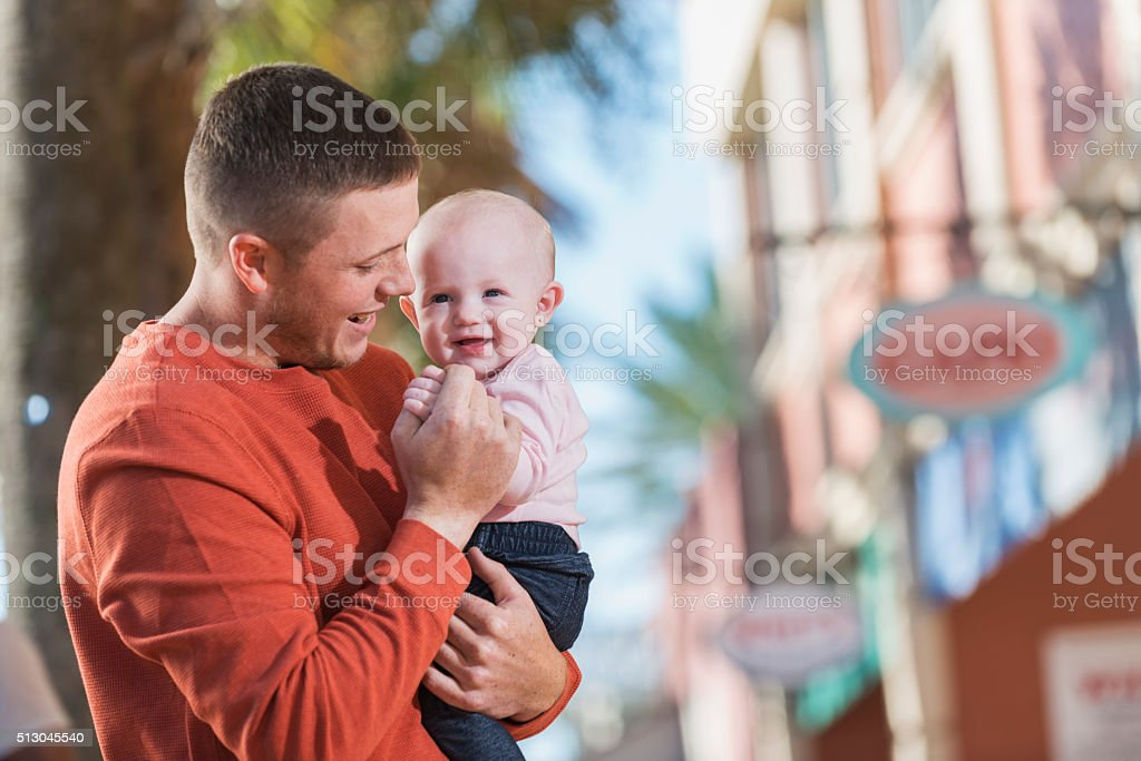Young man holding his baby girl outdoors stock photo