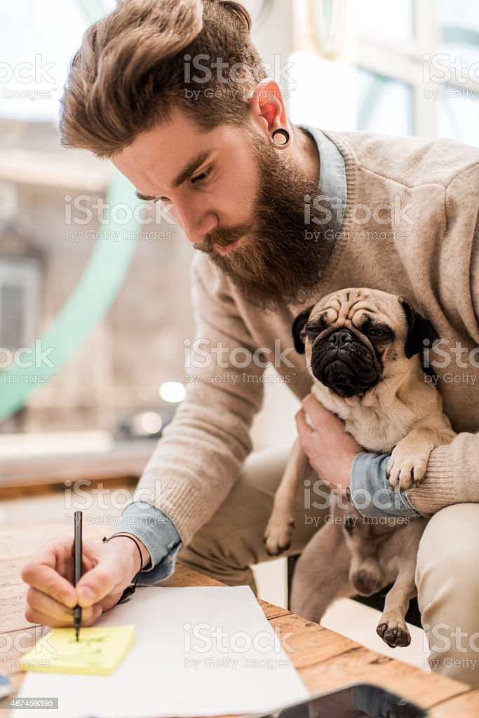 Young man holding his dog while taking notes. stock photo