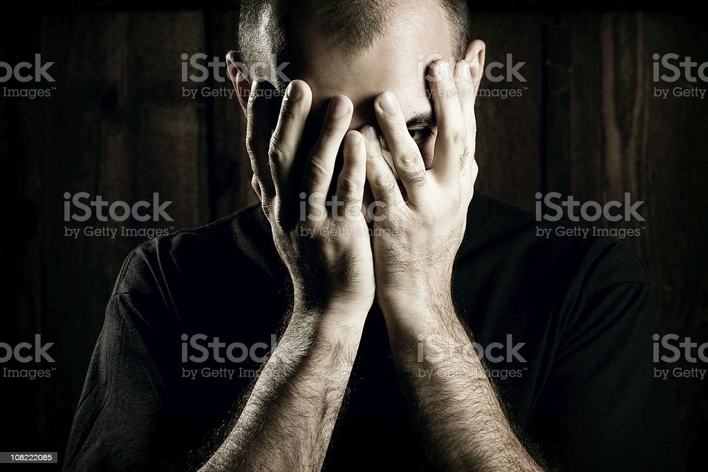 Young Man Holding His Face in Hands, Low Key Lit royalty-free stock photo