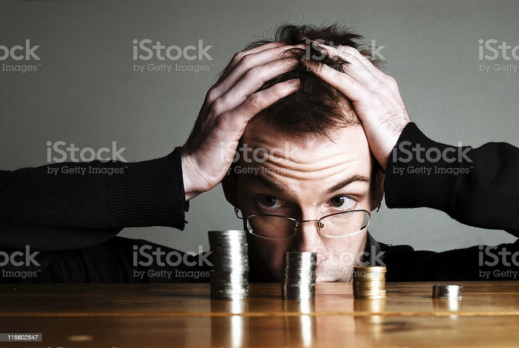 Young man holding his head counting pennies stock photo