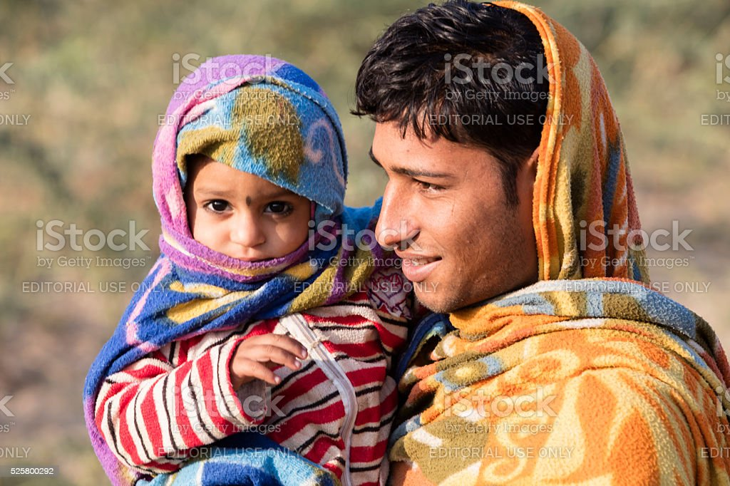 Young man holding his tiny son, Rajasthan, India stock photo