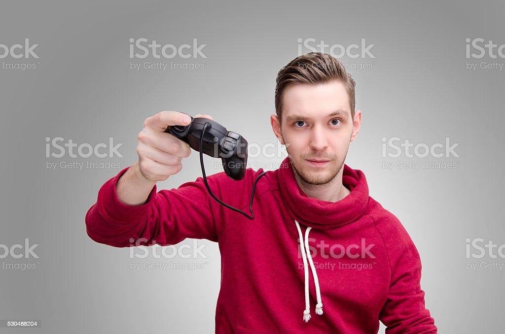 Young man holding joystick on gray background stock photo