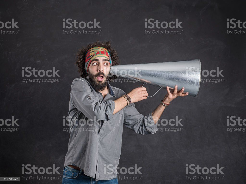 Young man holding megaphone to his ear stock photo