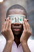 Young man holding money over eyes