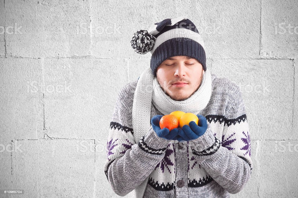 Young man holding natural vitamins in winter stock photo