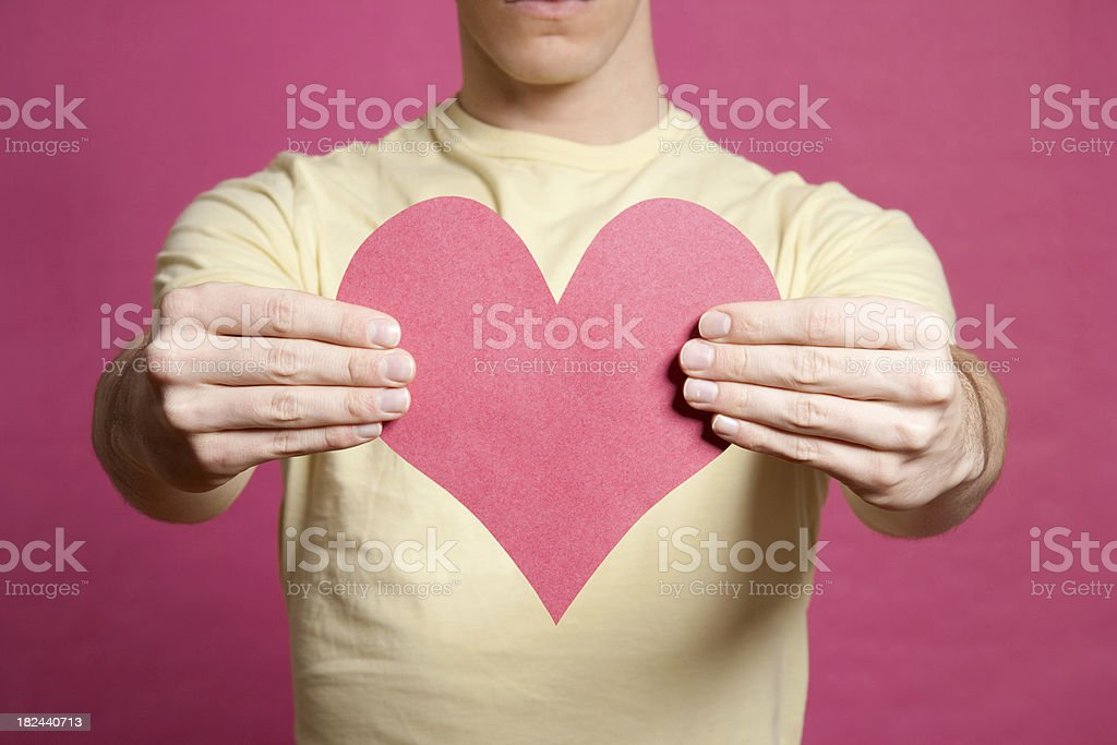 Young man holding pink heart shape royalty-free stock photo