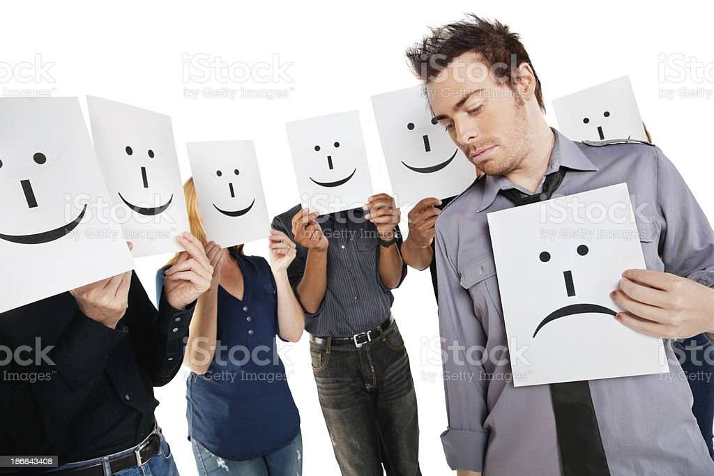 Young Man Holding Sad Face Among Happy People With Signs royalty-free stock photo