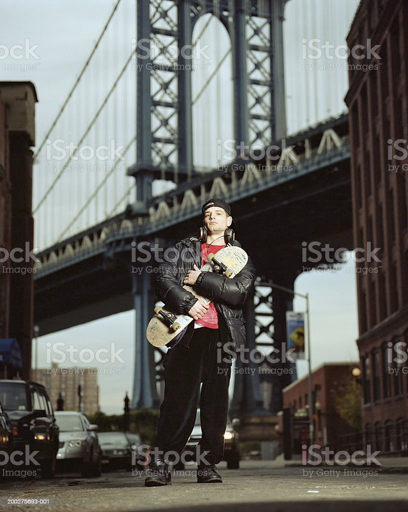 Young man holding skateboard, portrait, Manhattan Bridge in background stock photo