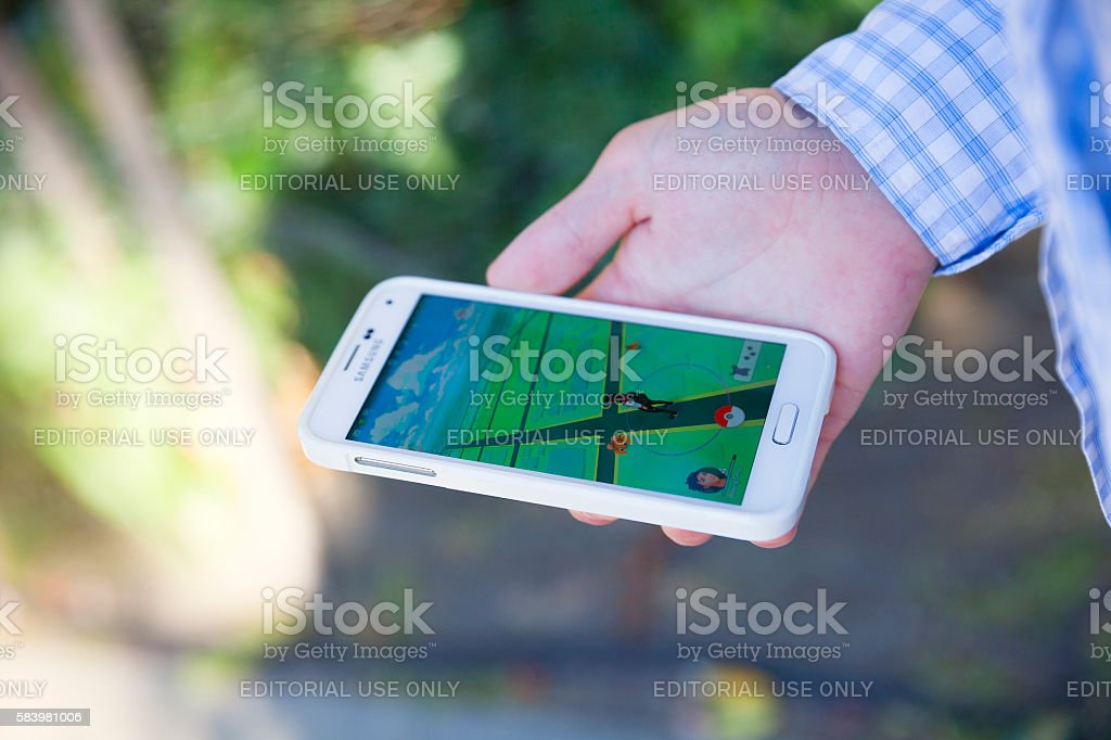 Young man holding smartphone playing Pokémon Go stock photo
