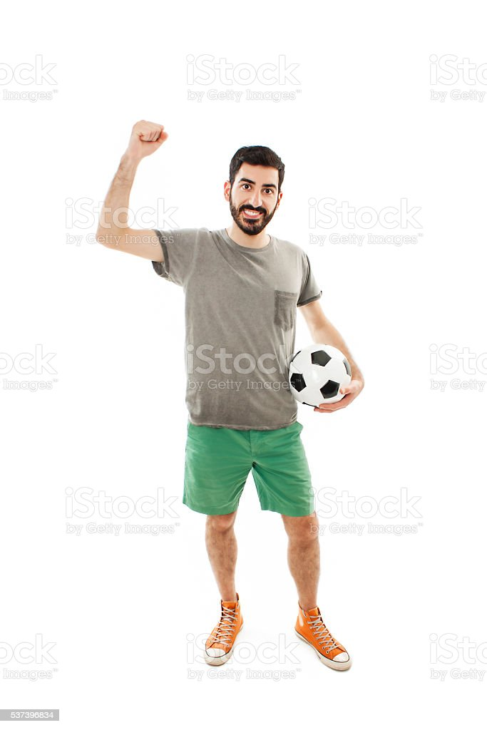 Young man holding soccer ball in hand. He's happy stock photo