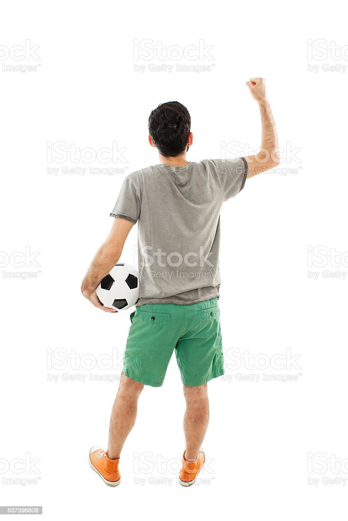 Young man holding soccer ball in hand looking at wall stock photo