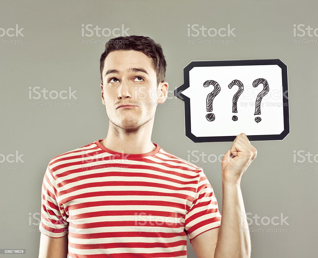 Young man holding speech bubble with question marks stock photo