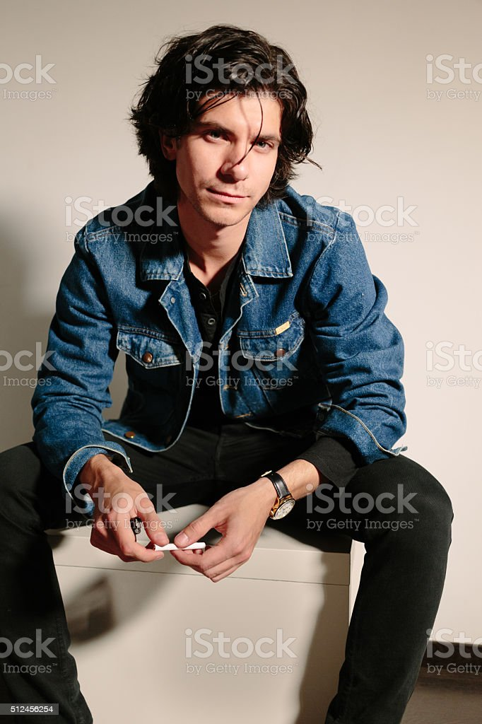Young man holds a cigarette in hand and sits on stock photo