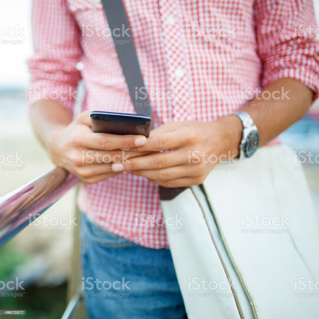 Young man holds a smart phone in his hand outdoors stock photo