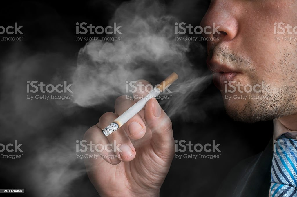 Young man holds cigarette and smoking. Low key photo. stock photo