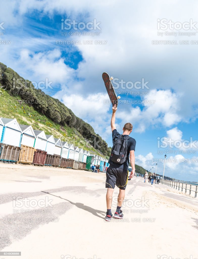 Young man holds up a skateboard walking along Bournemouth Beach stock photo