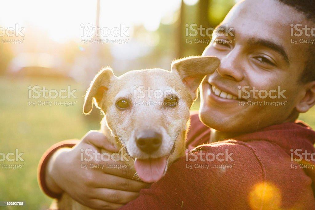 young man hug his small Mixed-breed dog, looking at camera stock photo