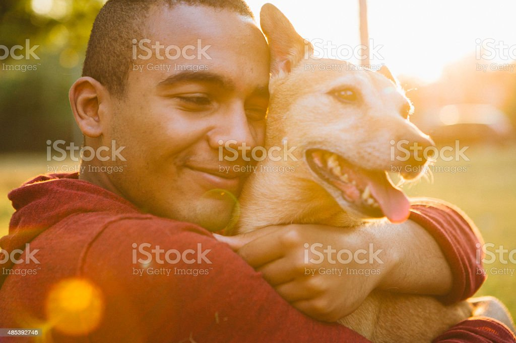 young man hug his small Mixed-breed dog stock photo