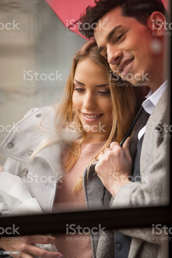 Young man hugging a girlfriend under the umbrella stock photo