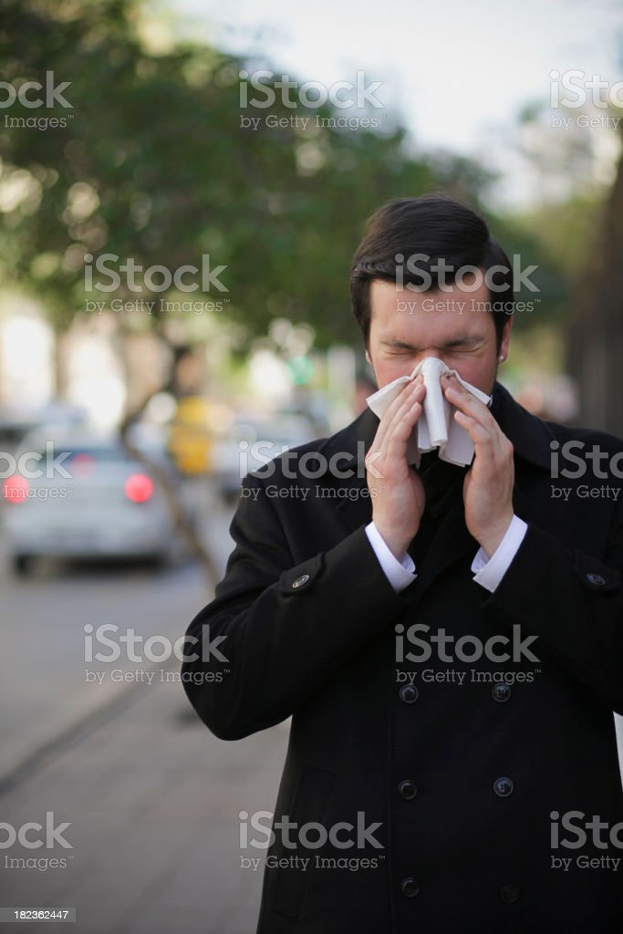 A young man in a black coat blowing his nose with a tissue royalty-free stock photo