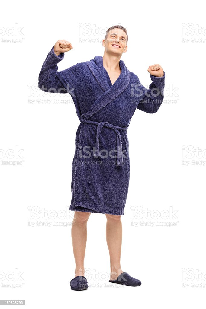 Young man in a blue bathrobe stretching himself stock photo
