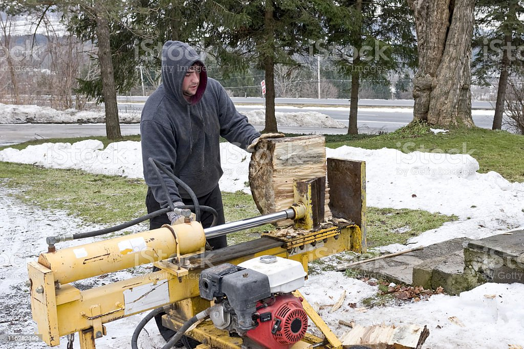 Young man in a hoodie jacket splitting wood royalty-free stock photo