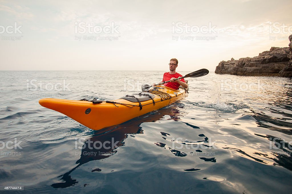 Young man in a kayak at sea stock photo