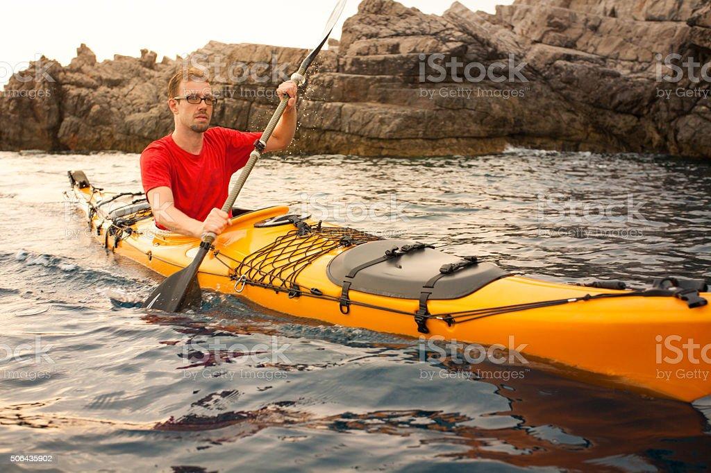 Young man in a kayak at sea stock photo
