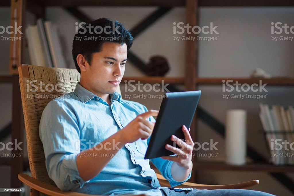 Young man in a rocking chair using digital tablet stock photo