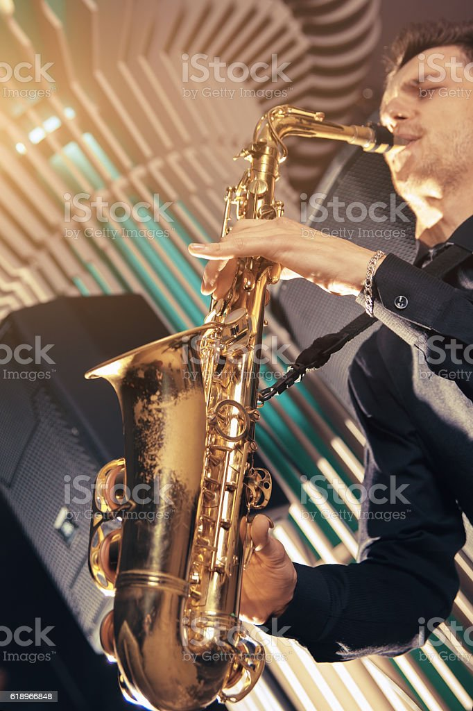 Young man in a suit hold saxophone stock photo