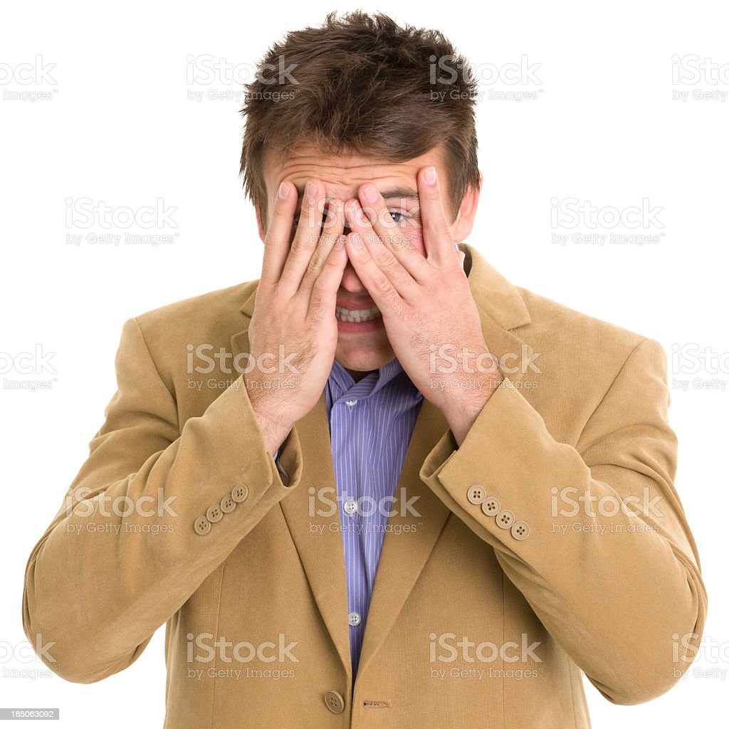 Young man in a tan suit peeking through his fingers royalty-free stock photo
