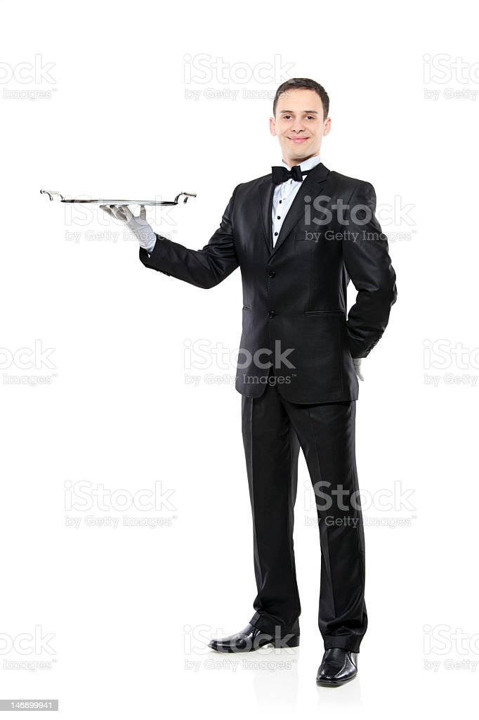 A young man in a tuxedo with a serving tray stock photo
