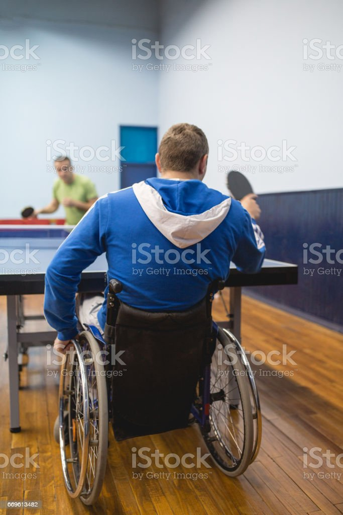 young man in a wheelchair is playing table tennis stock photo