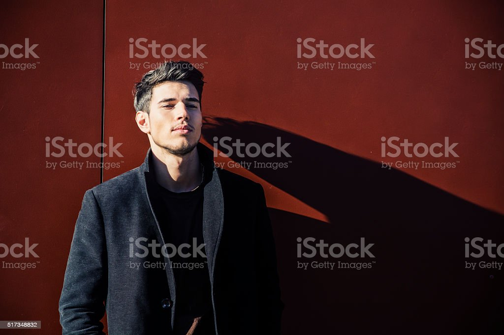 Young Man in a Winter Outfit Leaning on Red Wall stock photo