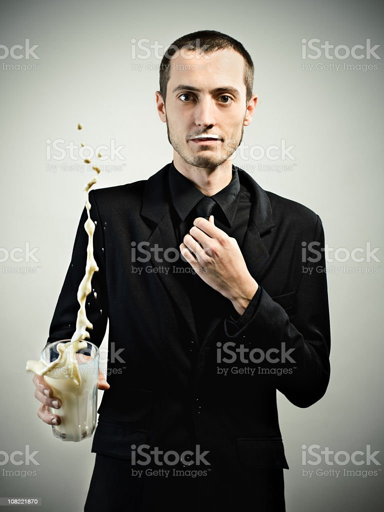 Young man in all black throwing glass of milk stock photo