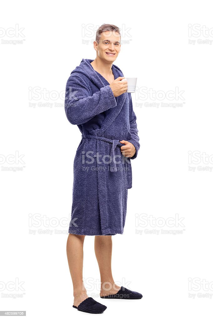 Young man in bathrobe holding a cup of coffee stock photo