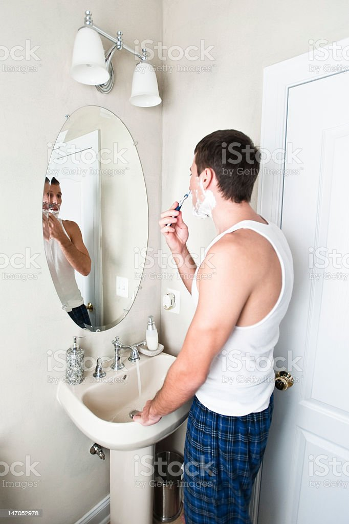 Young Man in Bathroom Shaving royalty-free stock photo