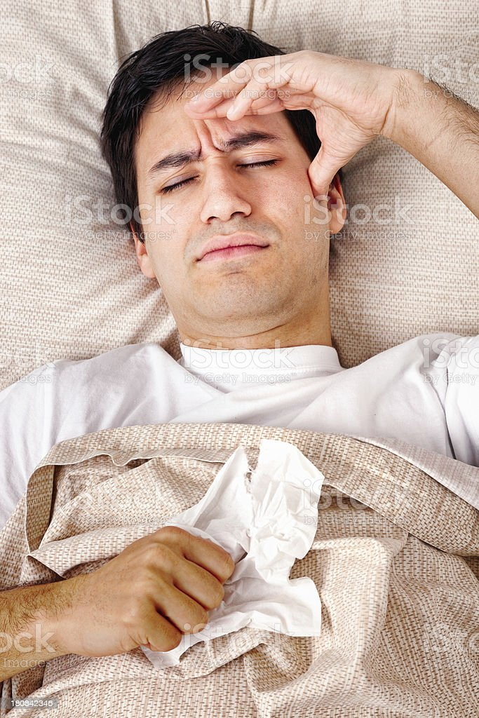 Young man in bed with bad headache flu cold royalty-free stock photo