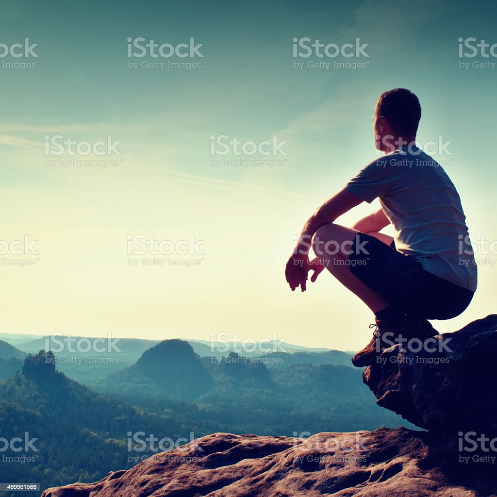 Young man in black pants and shirt sit on  edge stock photo