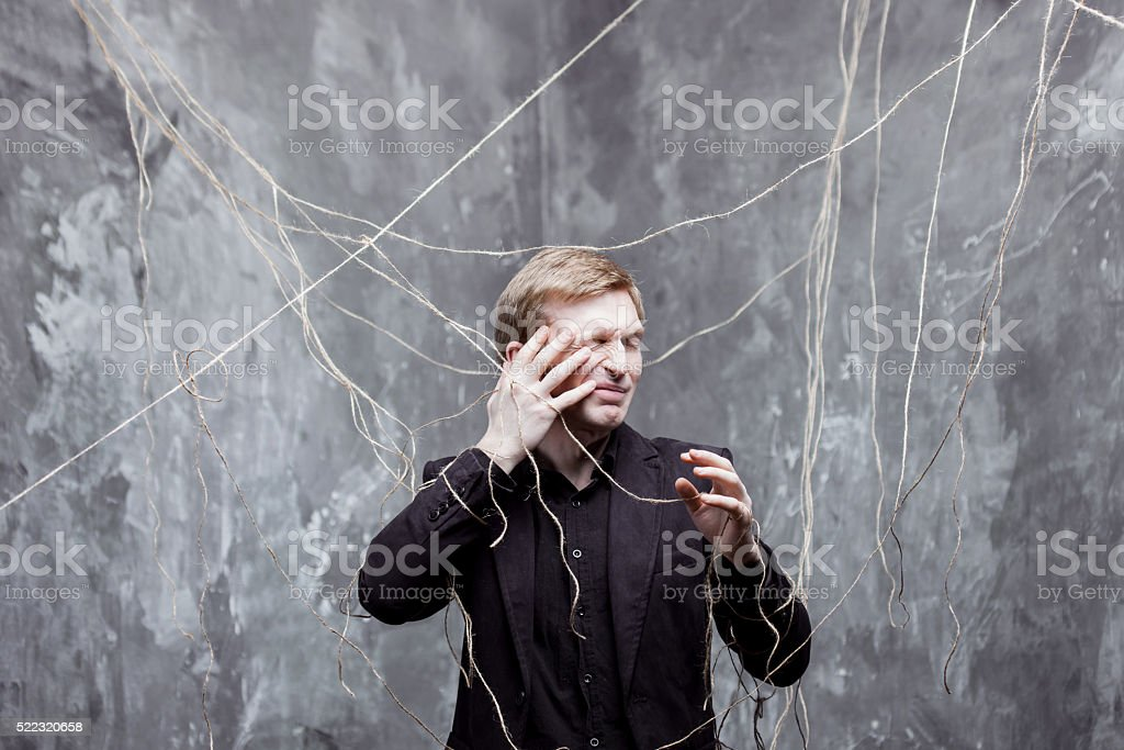 Young man in  black suit got caught on the web stock photo