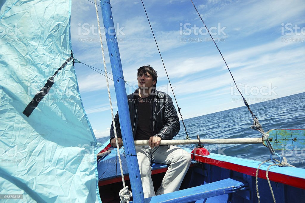 Young man in blue boat stock photo